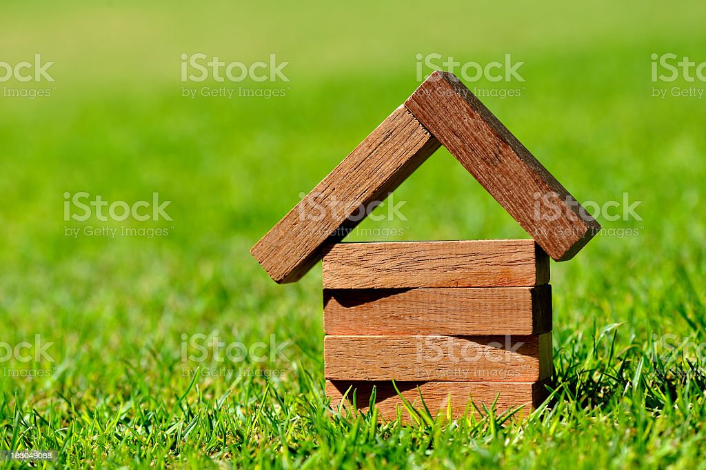 Close-up of blocks of wood forming a small house on grass stock photo