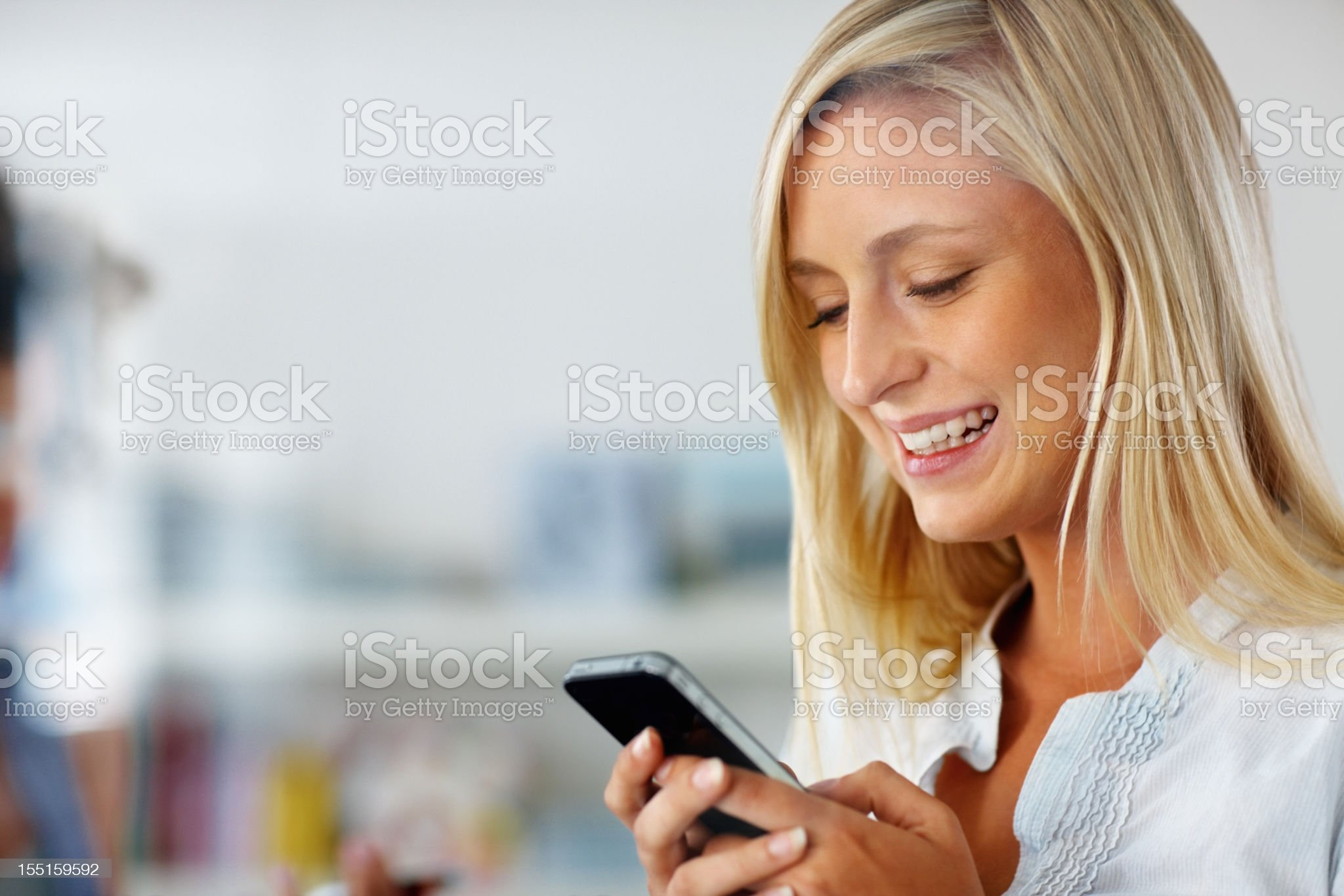 Close-up of blonde woman smiling while using smartphone royalty-free stock photo