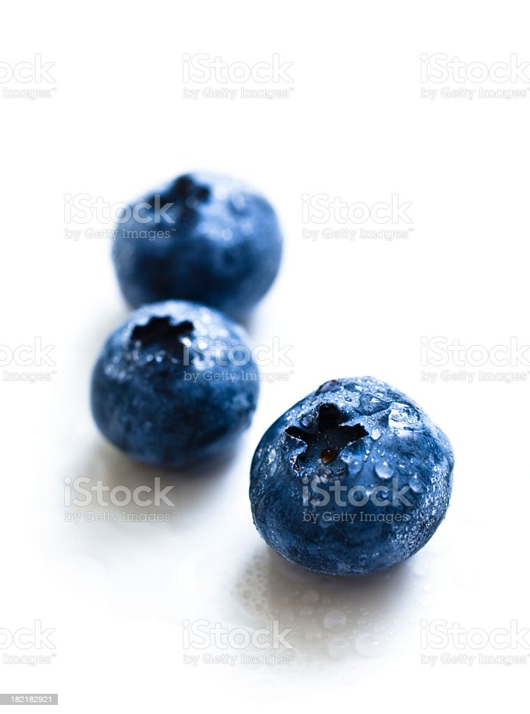 Close-up of blueberries with water drops on white background stock photo