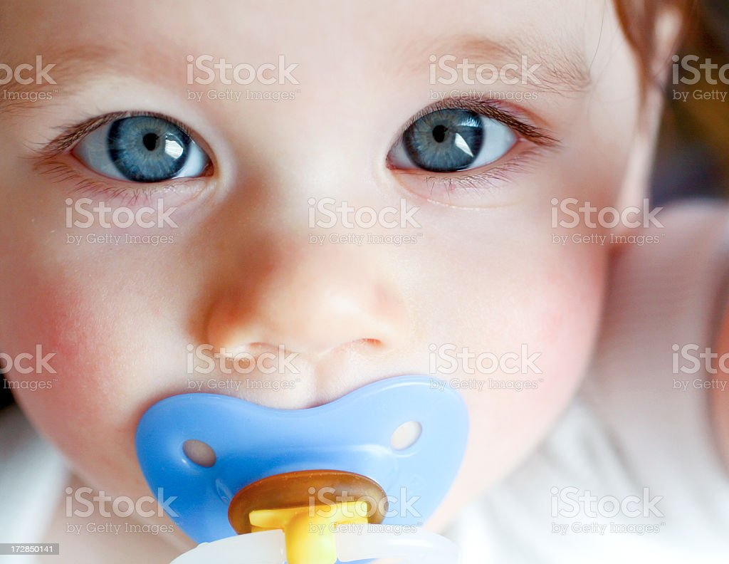 Close-up of blue-eyed baby with blue pacifier stock photo