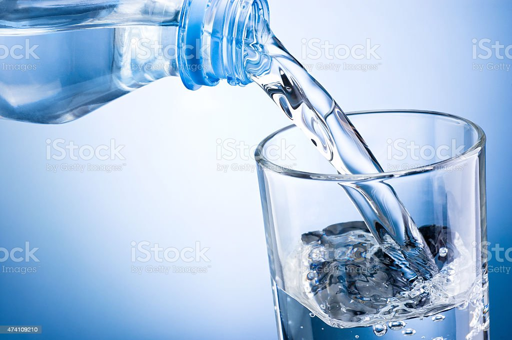 Closeup of bottle of water pouring into a glass stock photo