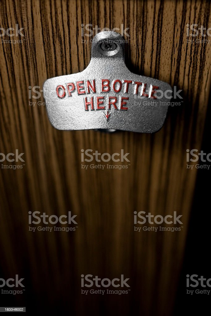 Close-up of bottle opener screwed into wooden board stock photo