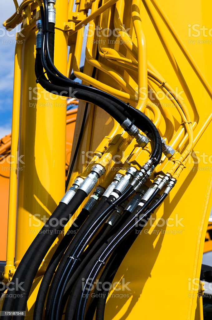 Close-up of bound black wires connecting yellow machinery stock photo