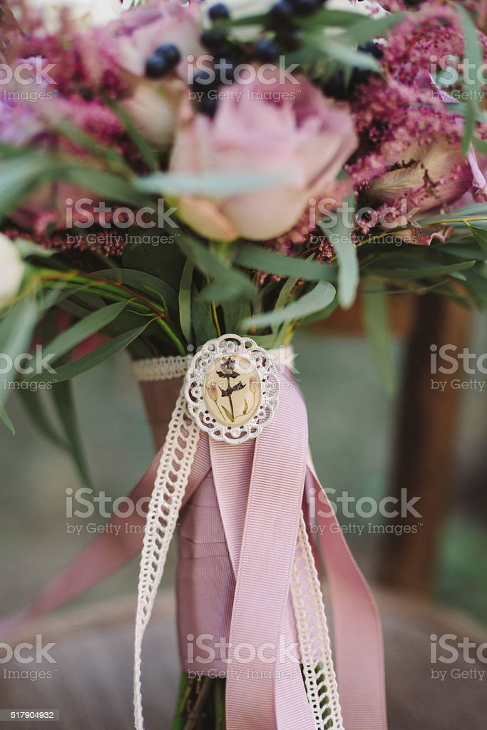 closeup of bouquet of roses and berries with vintage brooch stock photo