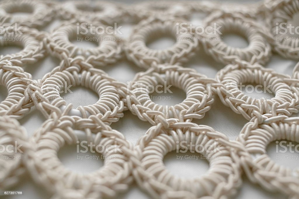 Close-up of braided cord pattern rings on white textured background. stock photo