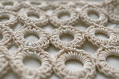 Close-up of braided cord pattern rings on white textured background.