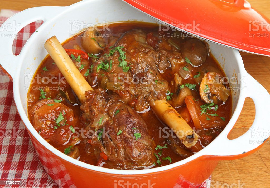 Close-up of braised lamb shanks in a casserole dish royalty-free stock photo