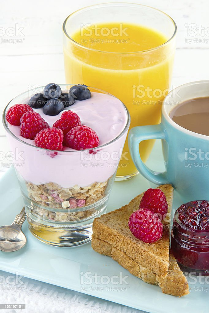 Closeup of breakfast with yoghurt, berries, juice, toast and coffee royalty-free stock photo