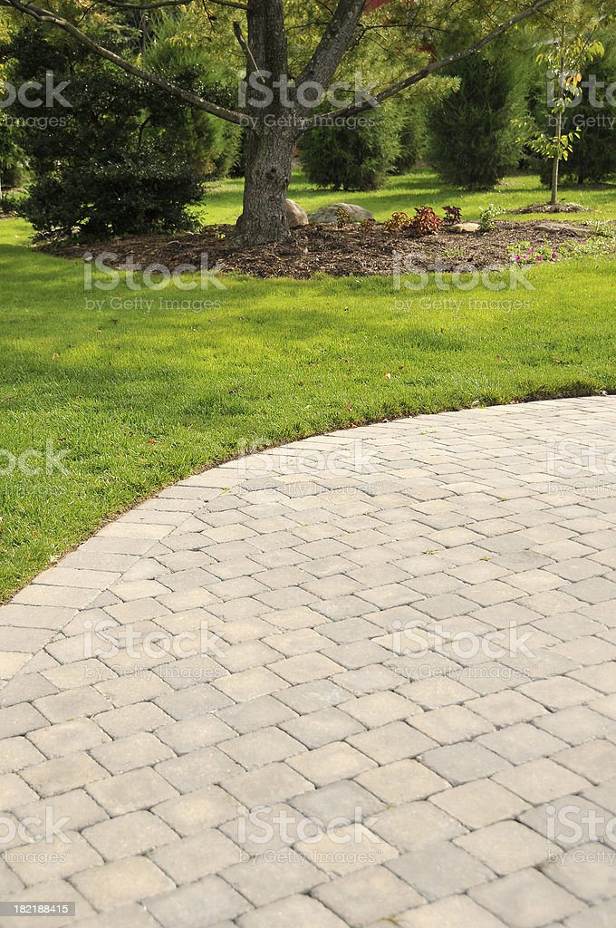 Close-up of brick patio with grass and trees in background royalty-free stock photo