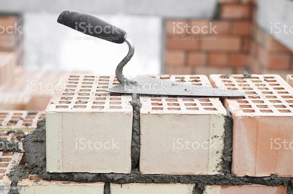 Close-up of bricklaying work, trowel, and mortared bricks stock photo