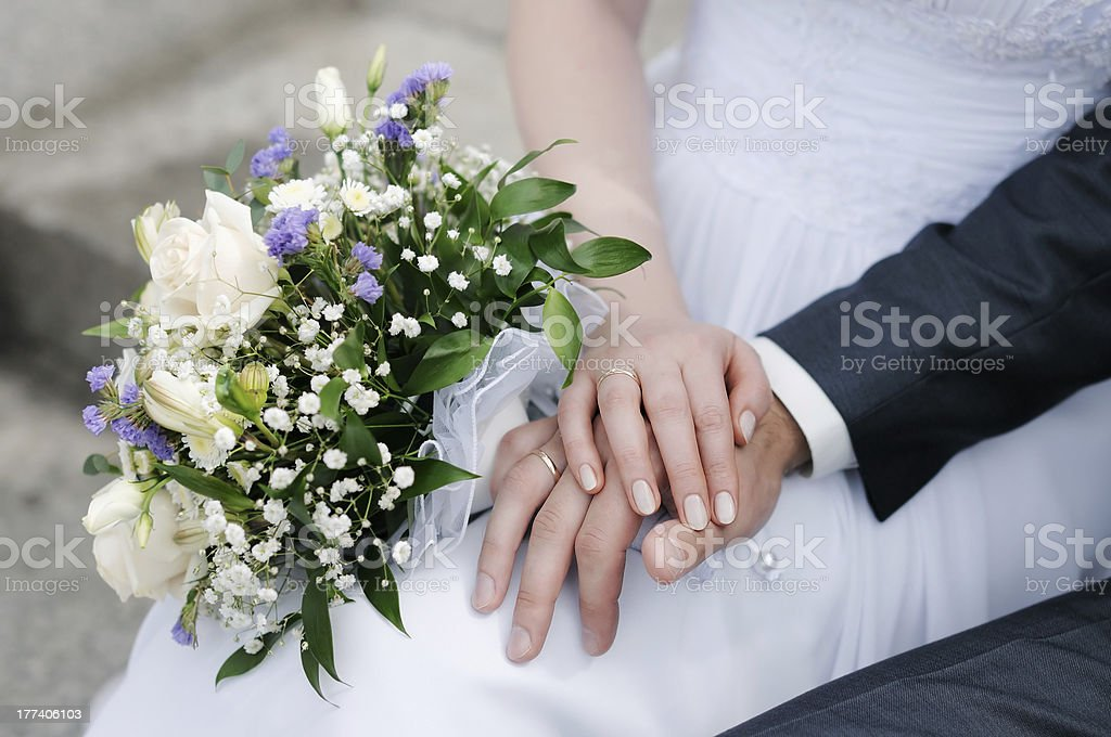 Closeup of bride and groom holding hands with flowers stock photo