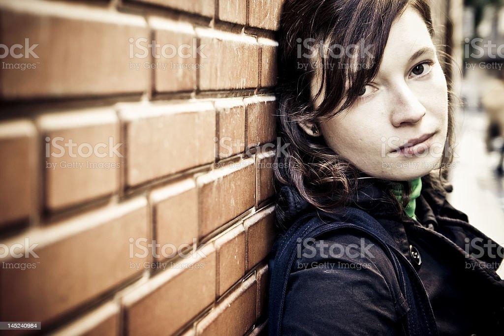 Close-up of brown and gray brick wall with yellow graffiti royalty-free stock photo