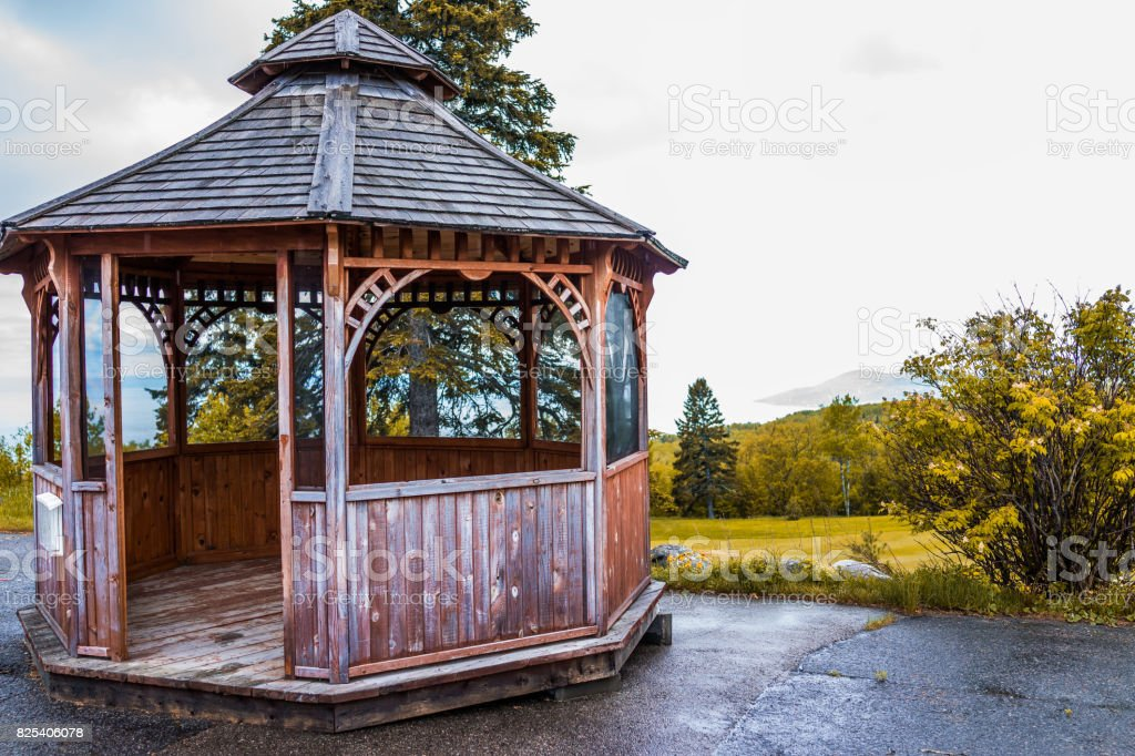 Closeup of brown empty gazebo in autumn landscape overlooking coast stock photo