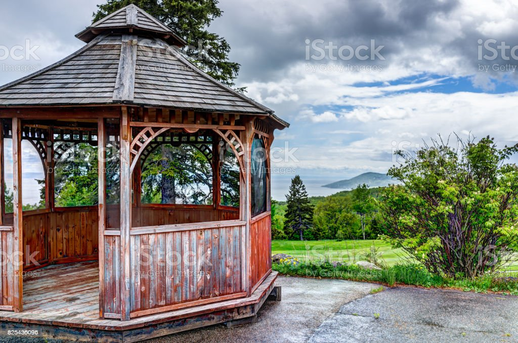 Closeup of brown empty gazebo in summer landscape overlooking coast stock photo