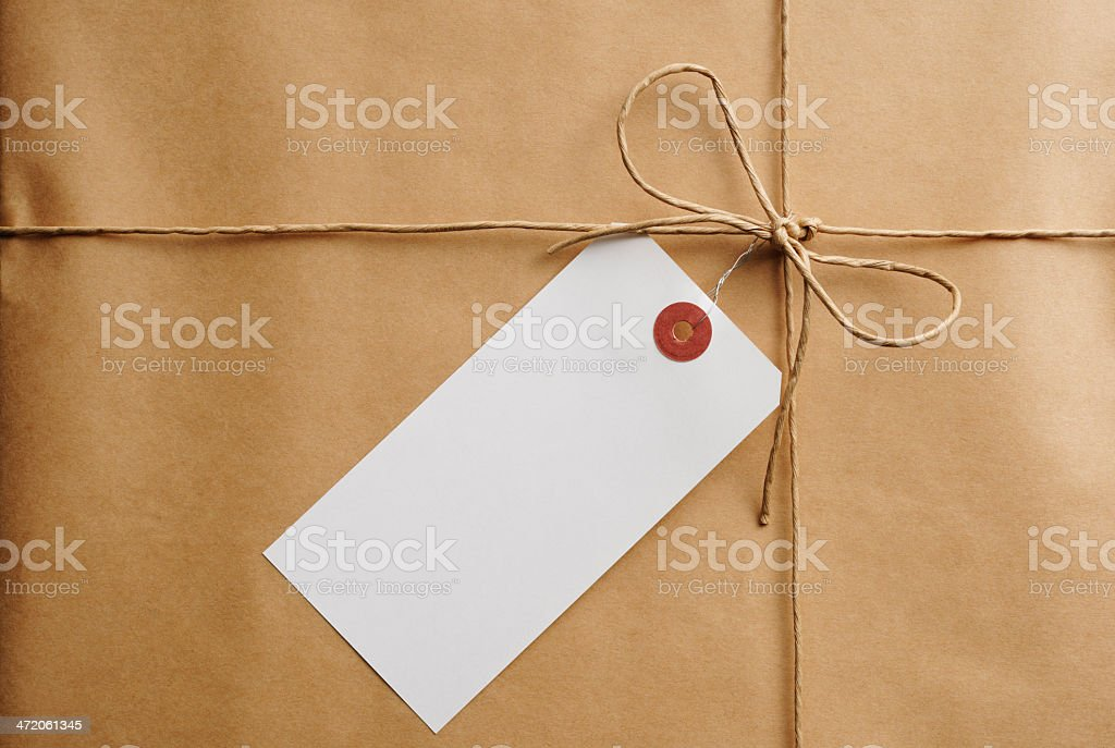 Close-up of brown package with a blank paper tag stock photo