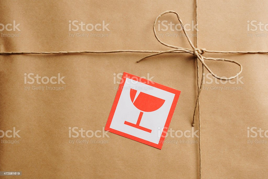 Close-up of brown package with a warning symbol stock photo