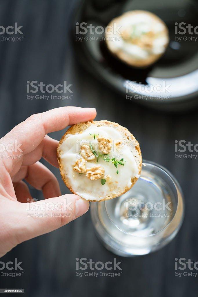 Closeup of bruschetta with Stracchino cheese, honey, walnuts and thyme stock photo