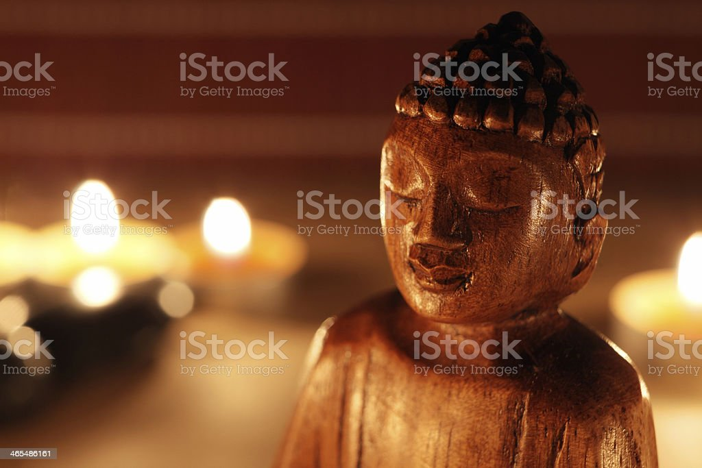 Close-up of Buddha statue with candles stock photo