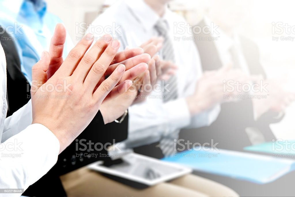 Close-up of business people clapping hands. stock photo