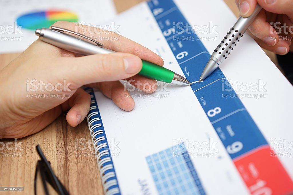 Close-up Of Business people  discussing  about a Date On Calendar stock photo