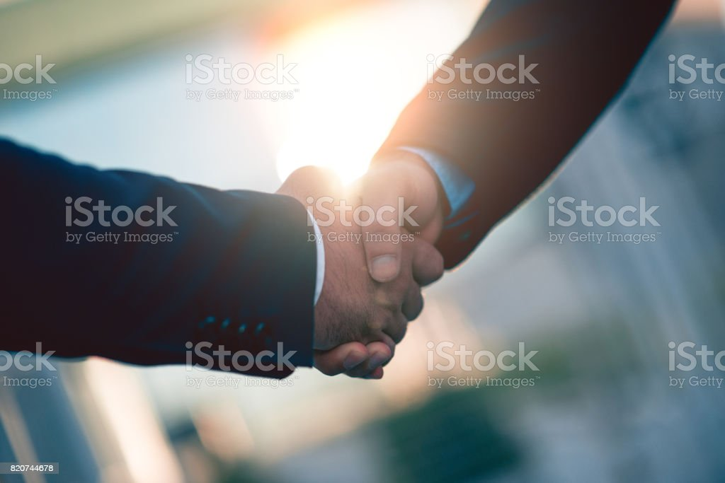 Close-up of Business People Hands Shaking on Sunset stock photo