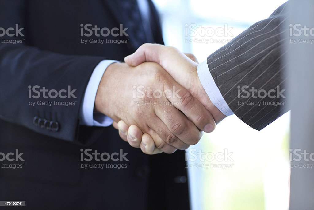 Closeup of business people shaking hands over a deal stock photo