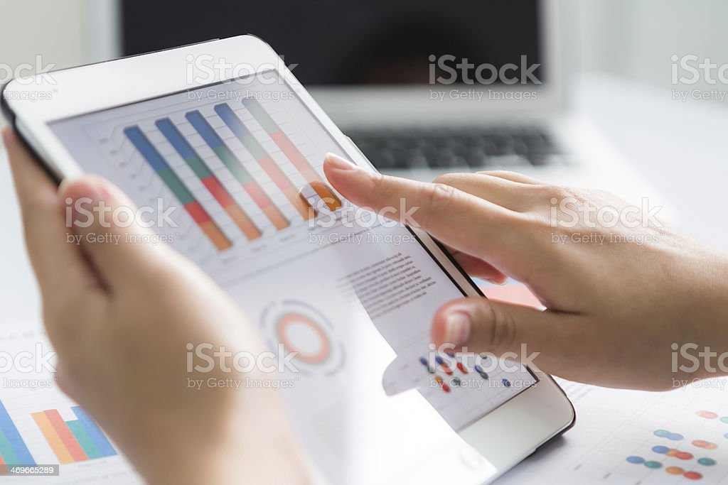 Close-up of business person using digital tablet with financial royalty-free stock photo