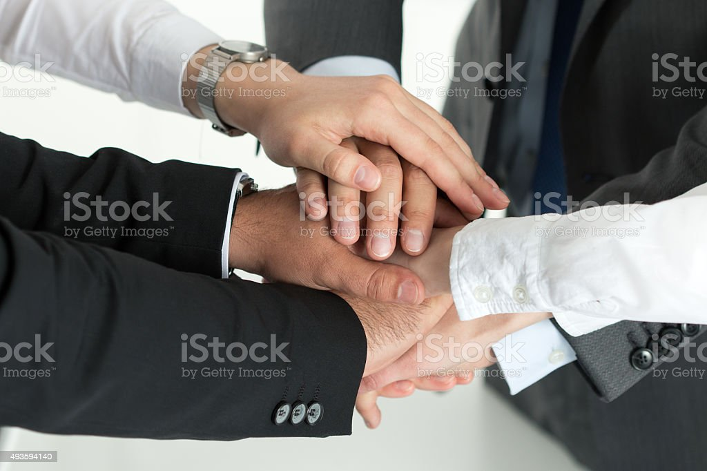 Closeup of business team showing unity with putting their hands stock photo