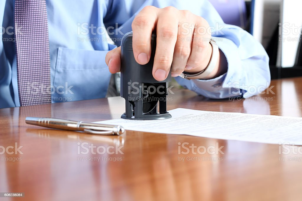Close-up Of Businessman Hand Pressing a  Stamp On Document stock photo