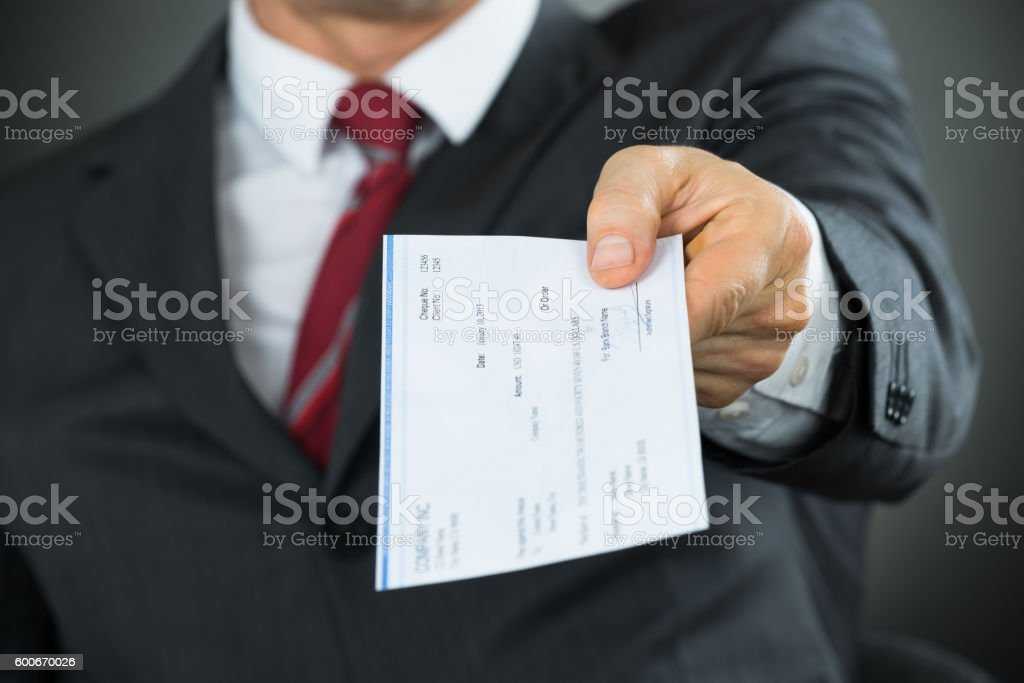 Close-up Of Businessman Hands Giving Cheque stock photo
