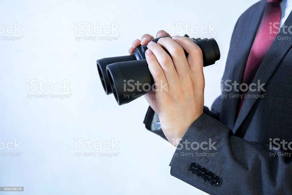 Close-up of Businessman looking for something with binoculars stock photo