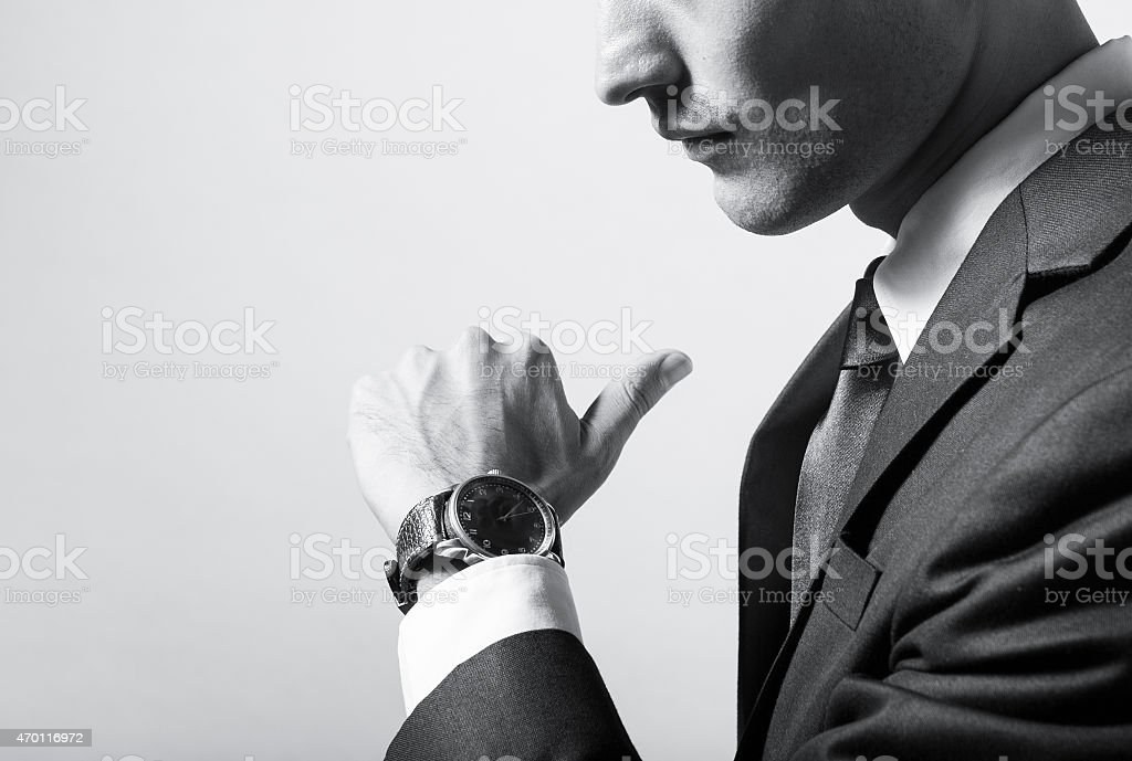 Close-up of businessman reading time on watch stock photo