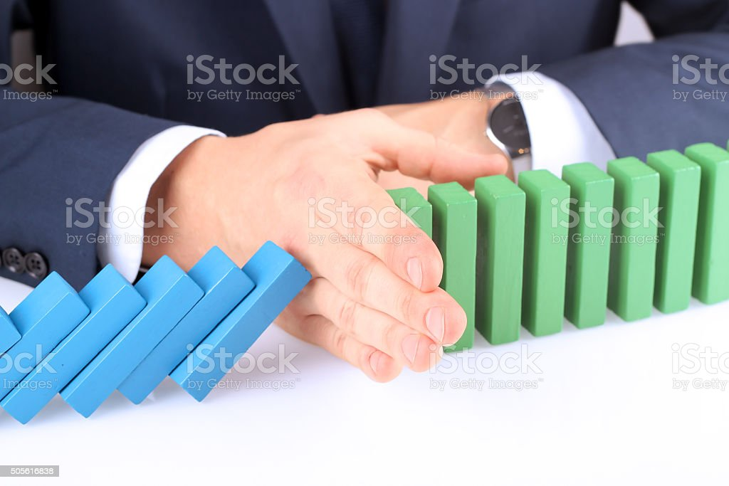 Close-up of businessman stopping the effect of domino with hand stock photo