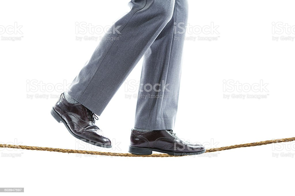 Close-up of Businessman Walking on Tight Rope stock photo