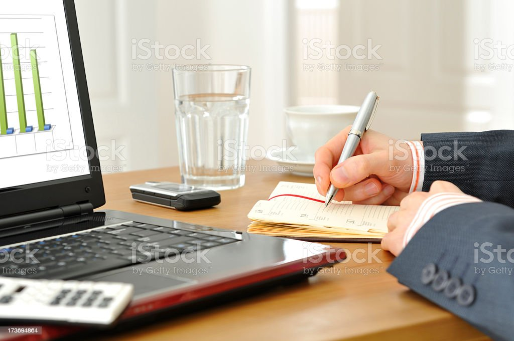 Close-up of businessman's hands making notes, laptop, chart, desk, office royalty-free stock photo