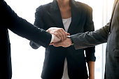Closeup of businesspeople pile hands