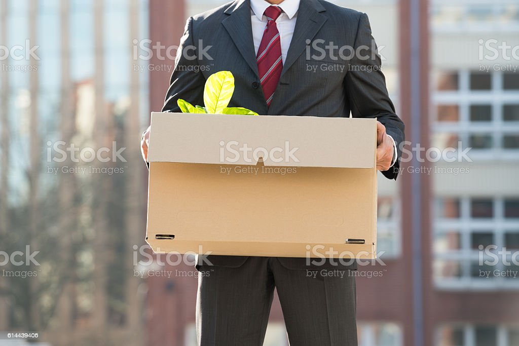 Close-up Of Businessperson Standing With Cardboard Box Outside O stock photo