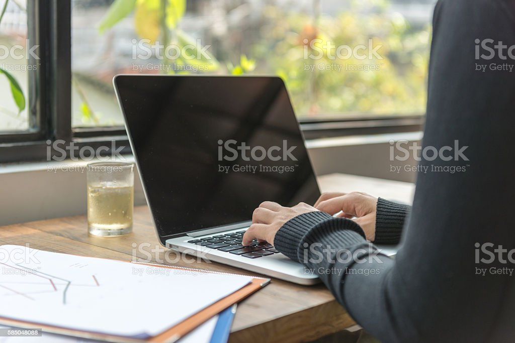 Close-up of businesswoman hand typing on laptop in her office stock photo