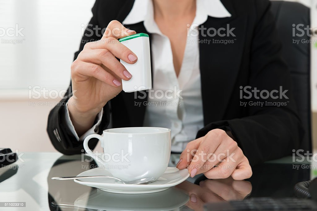 Close-up Of Businesswoman Putting Sugar In Cup stock photo