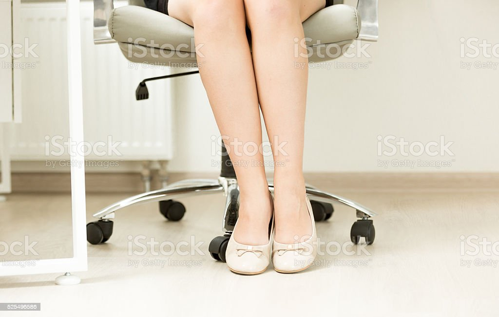 Closeup of businesswomen feet in ballet flats under office table stock photo