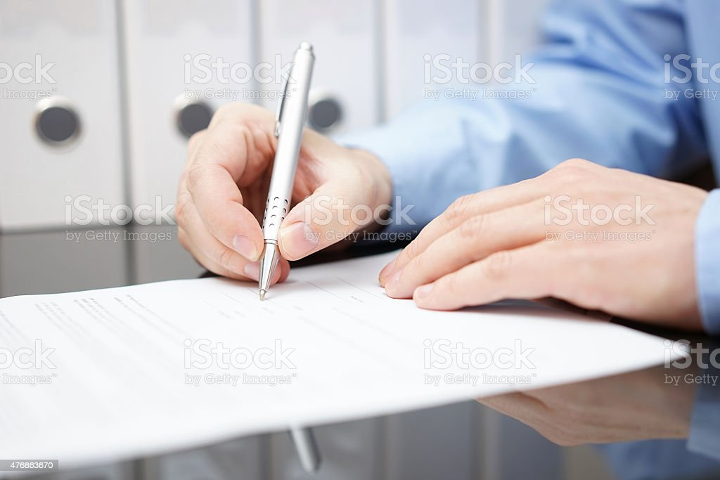 closeup of bussinessman is signing contract with documentation in background stock photo