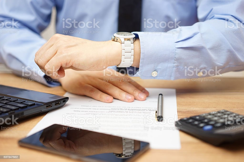 closeup of busy  Businessman watching his wrist watch  in office stock photo