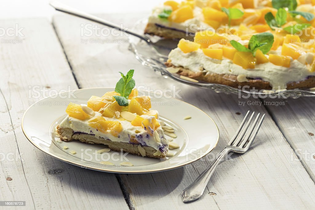 Closeup of cake with cream and peaches royalty-free stock photo