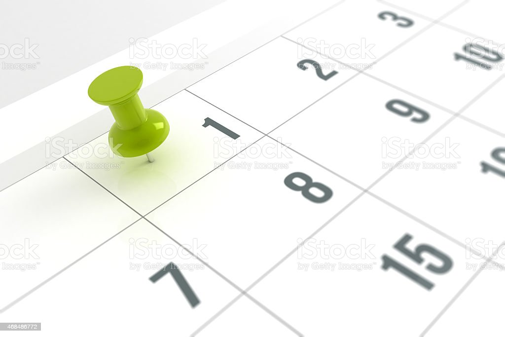 Close-up of calendar with green pushpin marked on day one stock photo