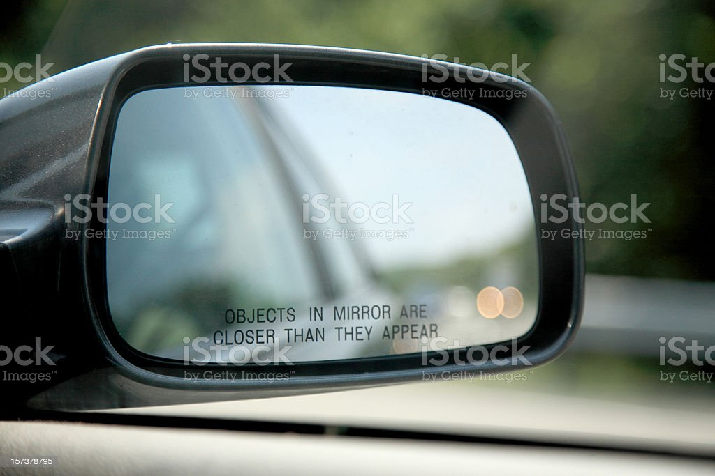 Close-up of car mirror objects are closer than they appear stock photo