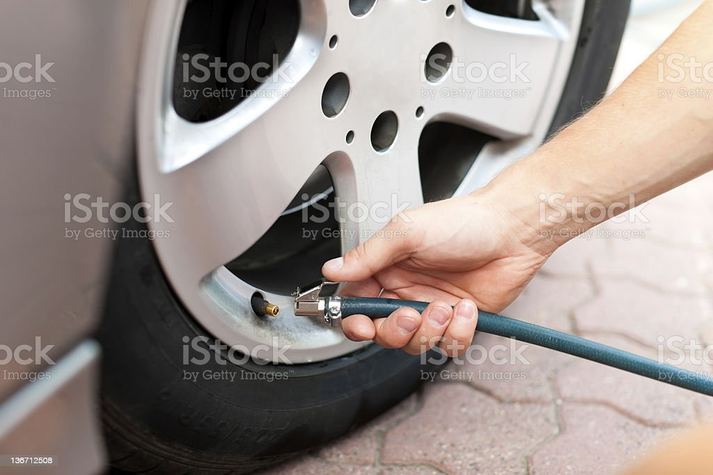 Close-up of car tire being aired up with hose by man's hand stock photo