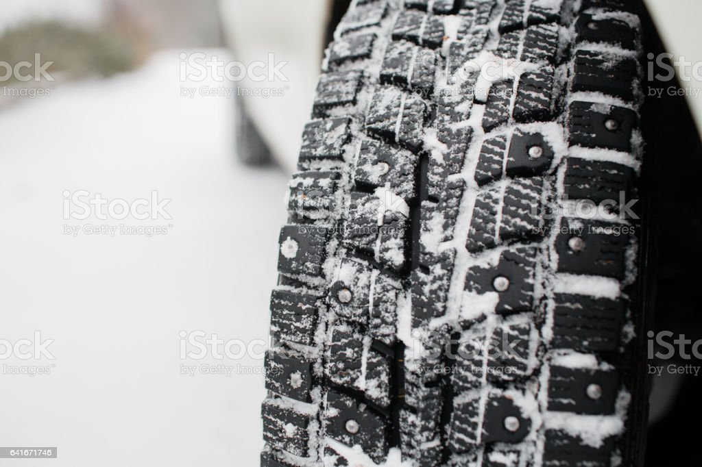 Closeup of car tires in winter. the first snow in late autumn stock photo