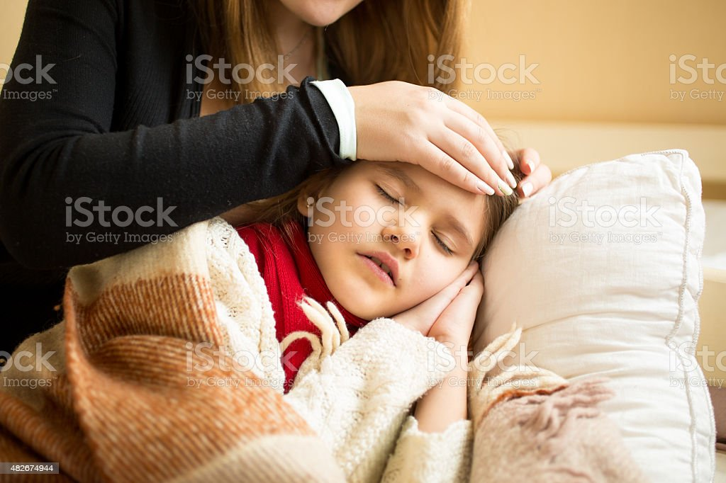 Closeup of caring mother holding head on sick daughter forehead stock photo