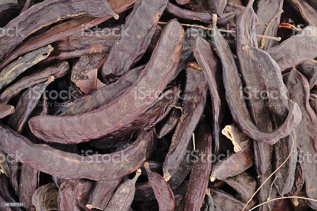 Closeup of carobs in a sack stock photo