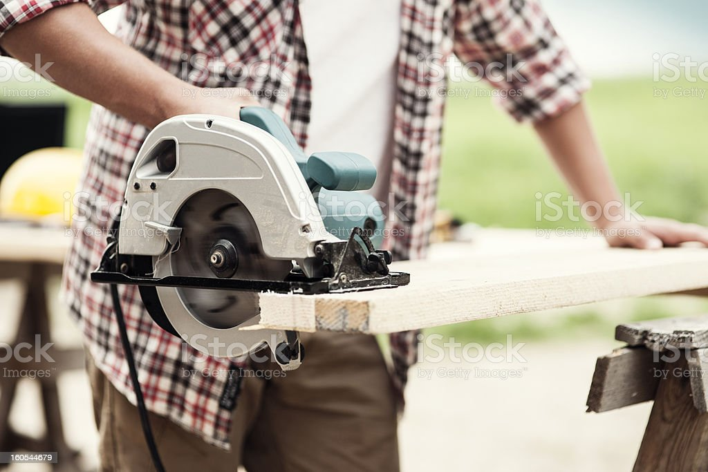 Close-up of carpenter cutting a wooden plank stock photo